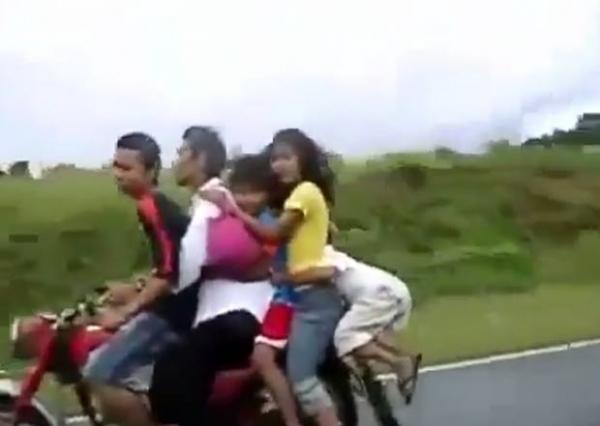 Garota é segura pela cabeça em moto superlotada na Ásia