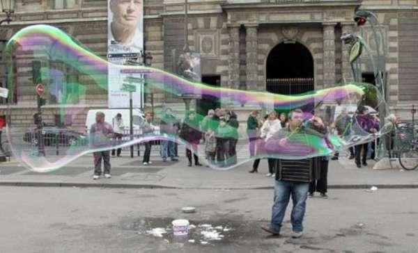 Artista exibe bolha de sabão gigante em praça de Paris