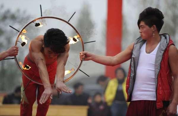 Chinês equilibra escada sobre queixo enquanto carrega a neta nos degraus