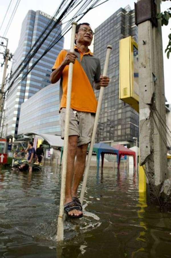 Tailandês é flagrado andando com pernas de pau em área alagada