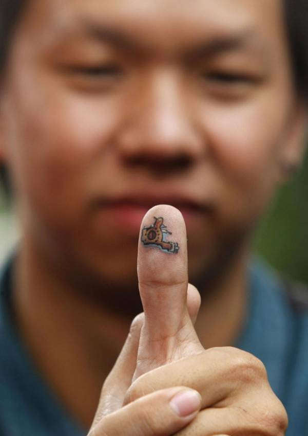 Tailandês exibe tatuagem no dedo polegar durante competição