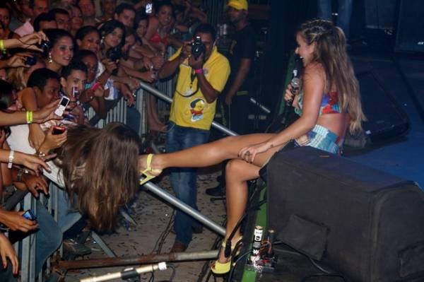 Fã saidinha beija pé esquerdo da cantora Alinne Rosa durante show