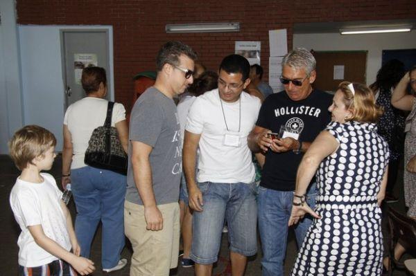 Usando sandálias iguais, Luciano Huck vai com o filho Joaquim votar