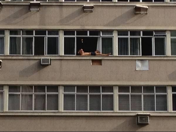 Homem se arrisca tomando sol em parapeito de 10º andar