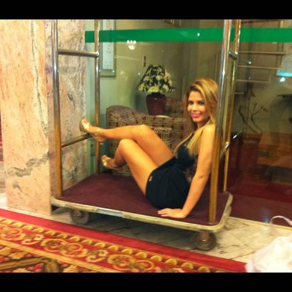 De vestidinho curto, ex-BBB Cacau sensualiza em maleiro de hotel