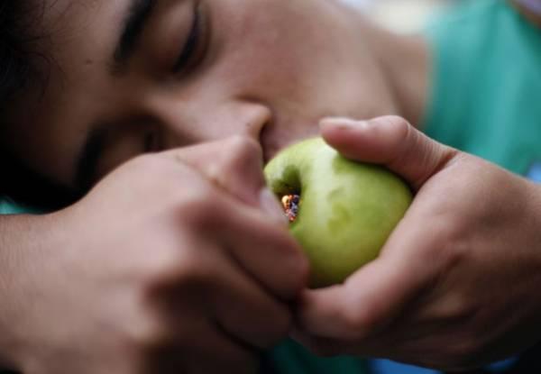 Homem cria cachimbo com maçã e fuma maconha em protesto