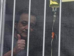 Homem faz vigília na porta de hospital com cartaz: