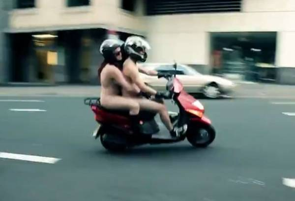 Casal anda nu de scooter por ruas de Sydney