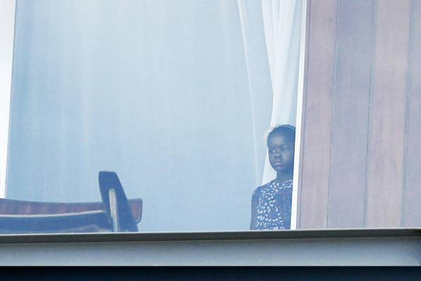 Acordada com fogos, Madonna espia atrás da cortina de janela do hotel
