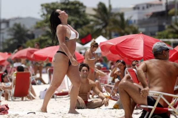 Cristina Mortágua tira a parte de cima do biquíni para pegar sol no Rio
