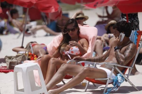Nicole Bahls curte praia com Victor Ramos, mas sem carinho