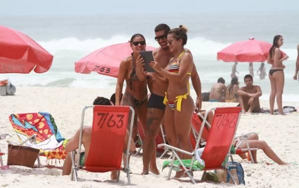 Ex-BBB Yuri troca beijos com morenaça tatuada em praia e dispara: