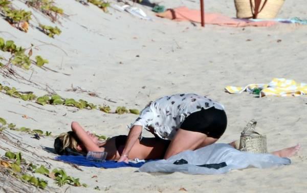 Em dia de namoro na  praia, Kate Moss vai ao mar e deixa seio
