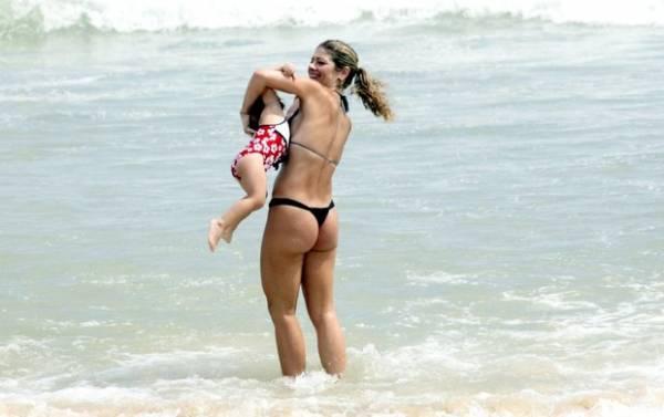Ex-paquita Cátia Paganote se diverte com a filha em praia