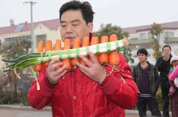 Músico chinês toca instrumento feito com cenouras em apresentação