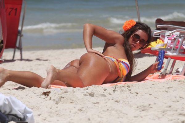 Nicole Bahls faz topless na praia e cultiva bronzeado para o carnaval