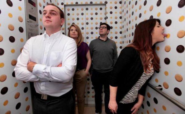 Consumidores lambem biscoitos adesivos em parede de elevador