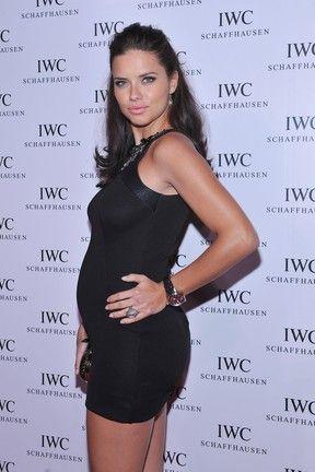 Grávida, Adriana Lima vai para inauguração com vestido colado