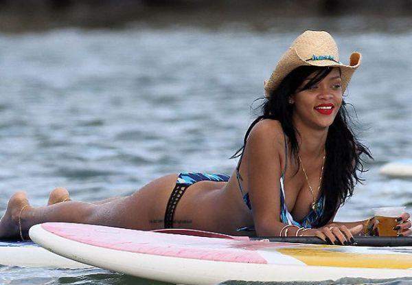 Rihanna toma cerveja em cima de prancha de surfe no Havaí