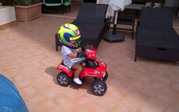 Filho de Massa pilota Ferrari de brinquedo com capacete do pai