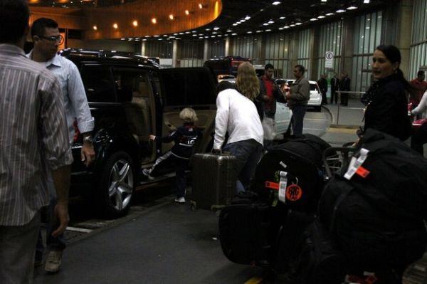 Angélica exibe barrigão no aeroporto com Huck e os dois filhos; veja fotos