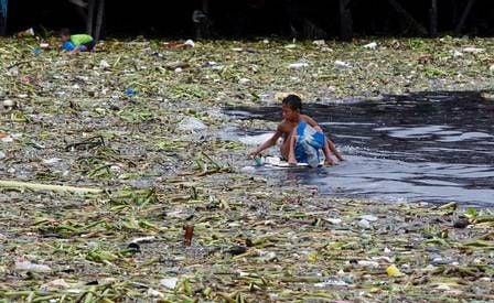 Após tempestade, filipinos nadam no lixo na tentativa de recuperar pertences