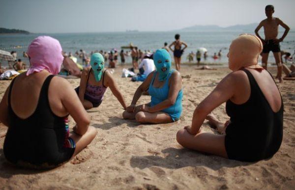 Chinesas vão à praia de máscara para proteger a pele