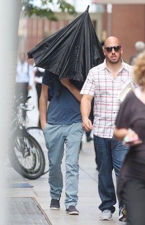 Leonardo DiCaprio usa guarda-chuva para se esconder de paparazzi