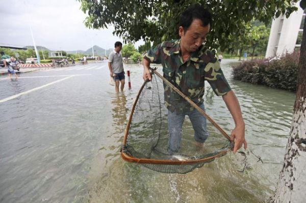 Homem pesca em rua alagada após passagem de tufão na China