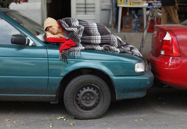 Mulher é flagrada tirando cochilo no capô de carro no México