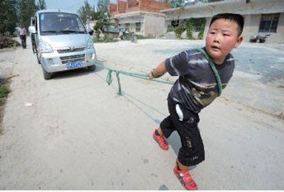 Chinês de 7 anos puxa van com oito adultos dentro