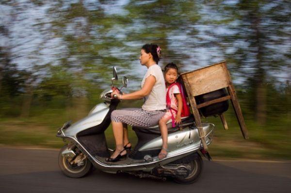 Chinesa é flagrada transportando filha e mesa em motoneta