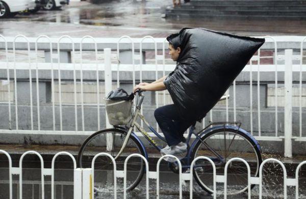 Mulher transforma saco de lixo em capa ao pedalar na chuva