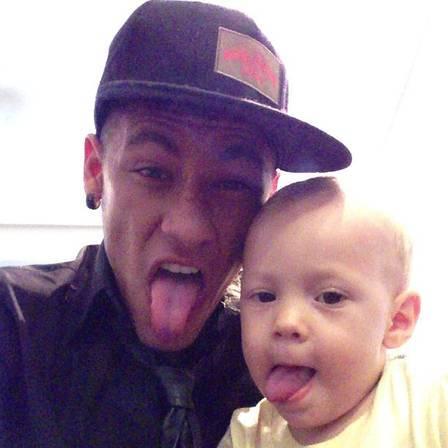 Neymar e o filho Davi Lucca posam mostrando a língua para foto