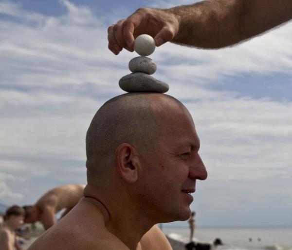 Russo se concentra para equilibrar pirâmide de pedras na cabeça