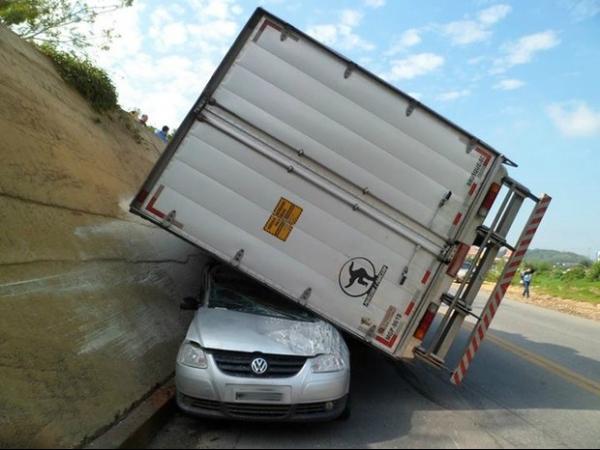 Condutor tem ferimentos leves após caminhão virar em cima de carro