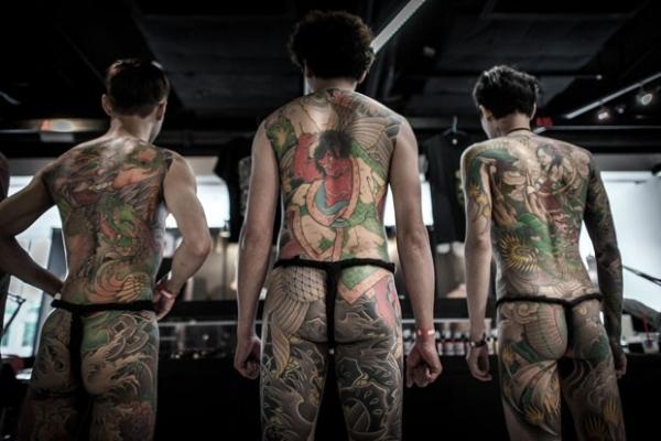 De tanga fio-dental, participantes exibem corpos tatuados na China
