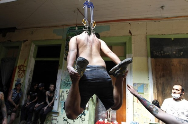 Participantes ficam pendurados por ganchos em festival no Chile