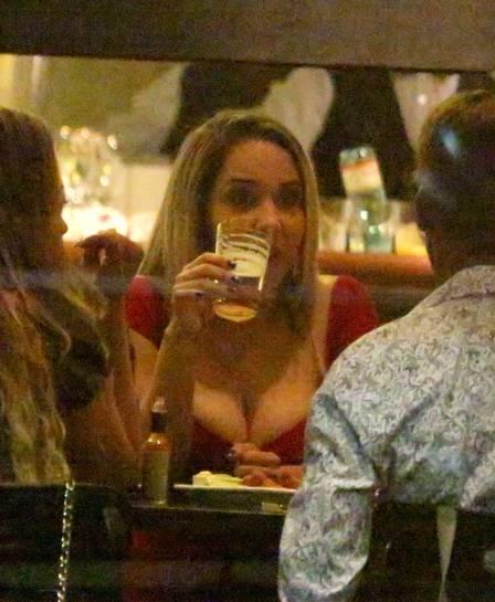 Mulher Melão chama atenção com vestido curtinho e decote profundo em bar chique da Zona Sul
