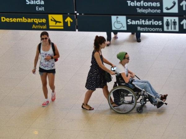 De cadeira de rodas, Maria Gadú embarca com a namorada