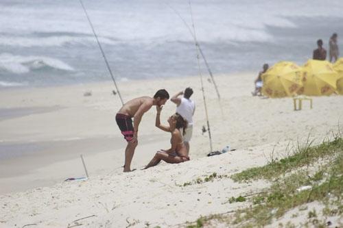 Fernanda de Freitas é beijada no pé pelo namorado em uma praia
