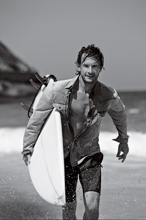 Rodrigo Santoro exibe corpo sarado e surfa para revista