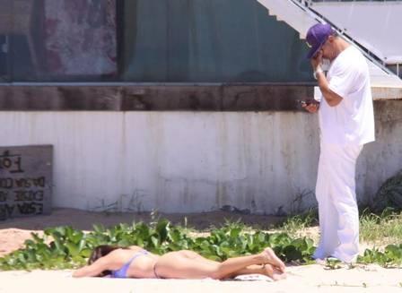 Namorada de Maurício Mattar pega sol com biquíni micro, enquanto ator só observa, vestido todo de branco