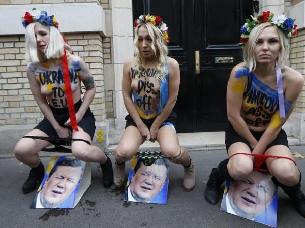 Ativistas do Femen urinam sobre fotos de presidente da Ucr穗ia