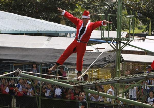 Papai Noel anda em corda bamba sobre piscina infestada de crocodilos