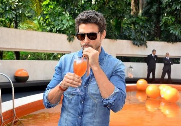 Com pinta de galã, Cauã Reymond toma drink em evento
