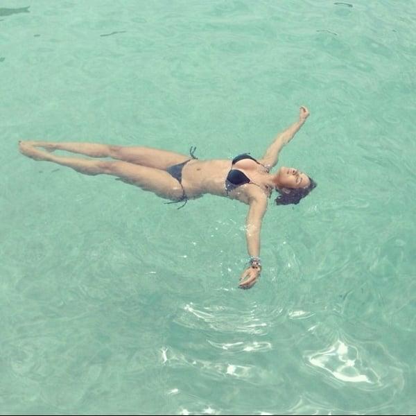 Namorada de Daniel Alves relaxa na piscina e posta foto de biquíni