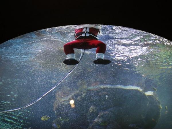 Papai Noel interage com turistas sob a água em aquário de Cingapura