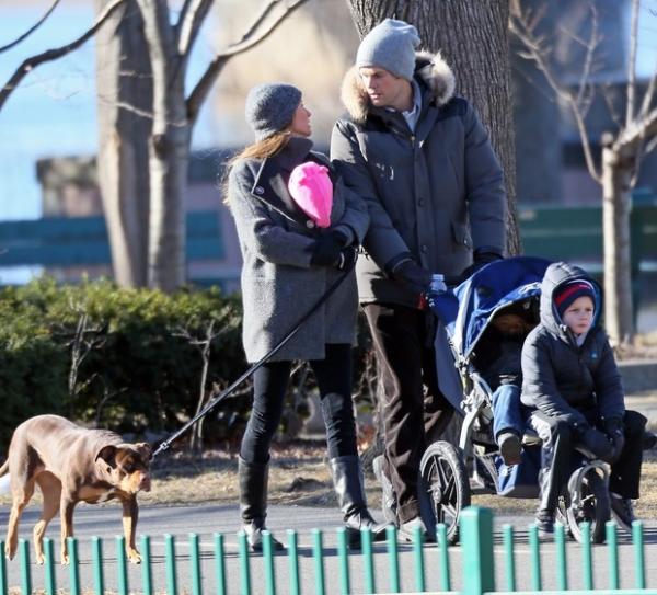 Gisele Bündchen carrega a filha dentro do casaco em parque