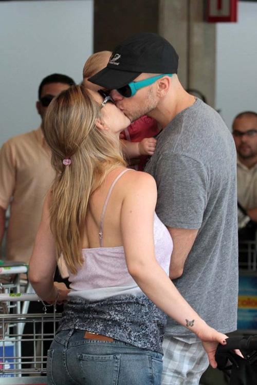 Com a filha no colo, Xuxa dá beijinho em Sheila Mello após desembarque